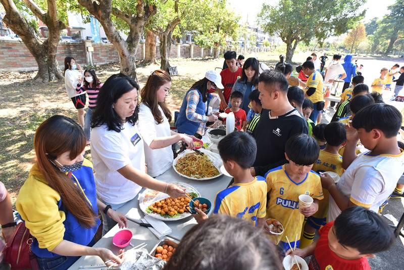埔里山城足球俱樂部與星河黑旋風球員友誼賽,熱心家長料理美味佳餚,雙方球員一起享用。(圖/牛爸攝)